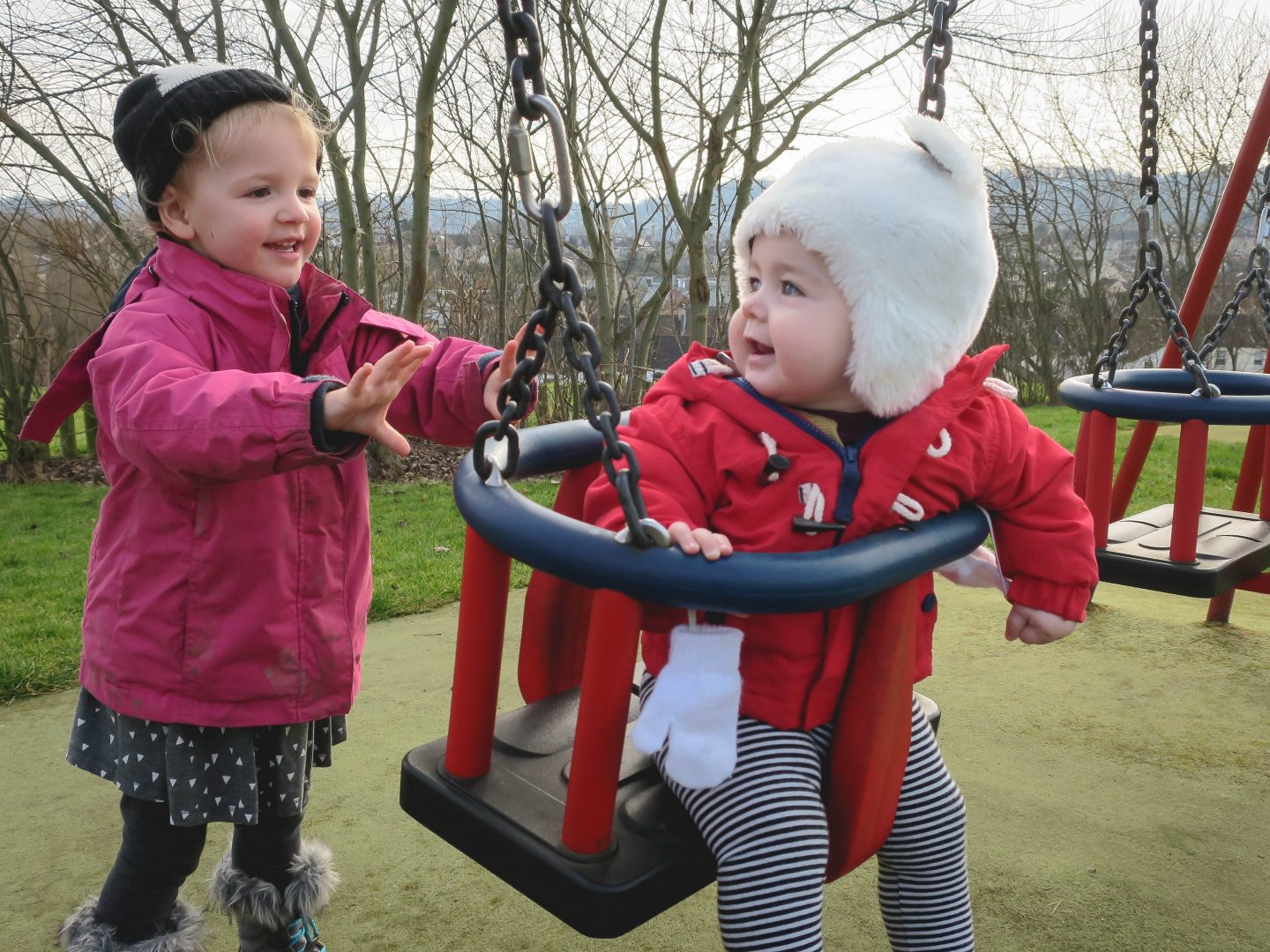 Toddler Pushing Baby on Swings