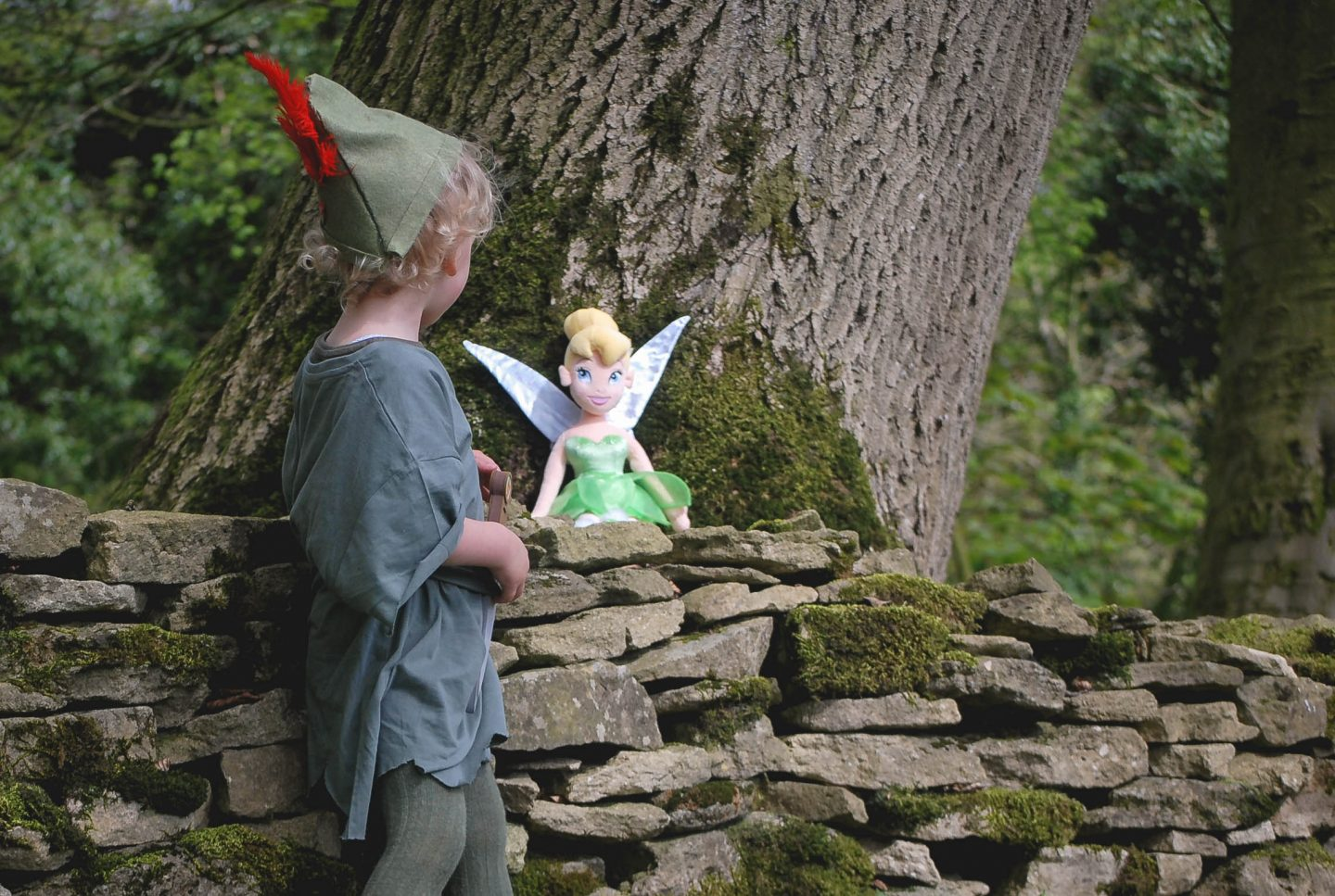 My daughter dressed as Disney's Peter Pan talking to Tinkerbell in the woods