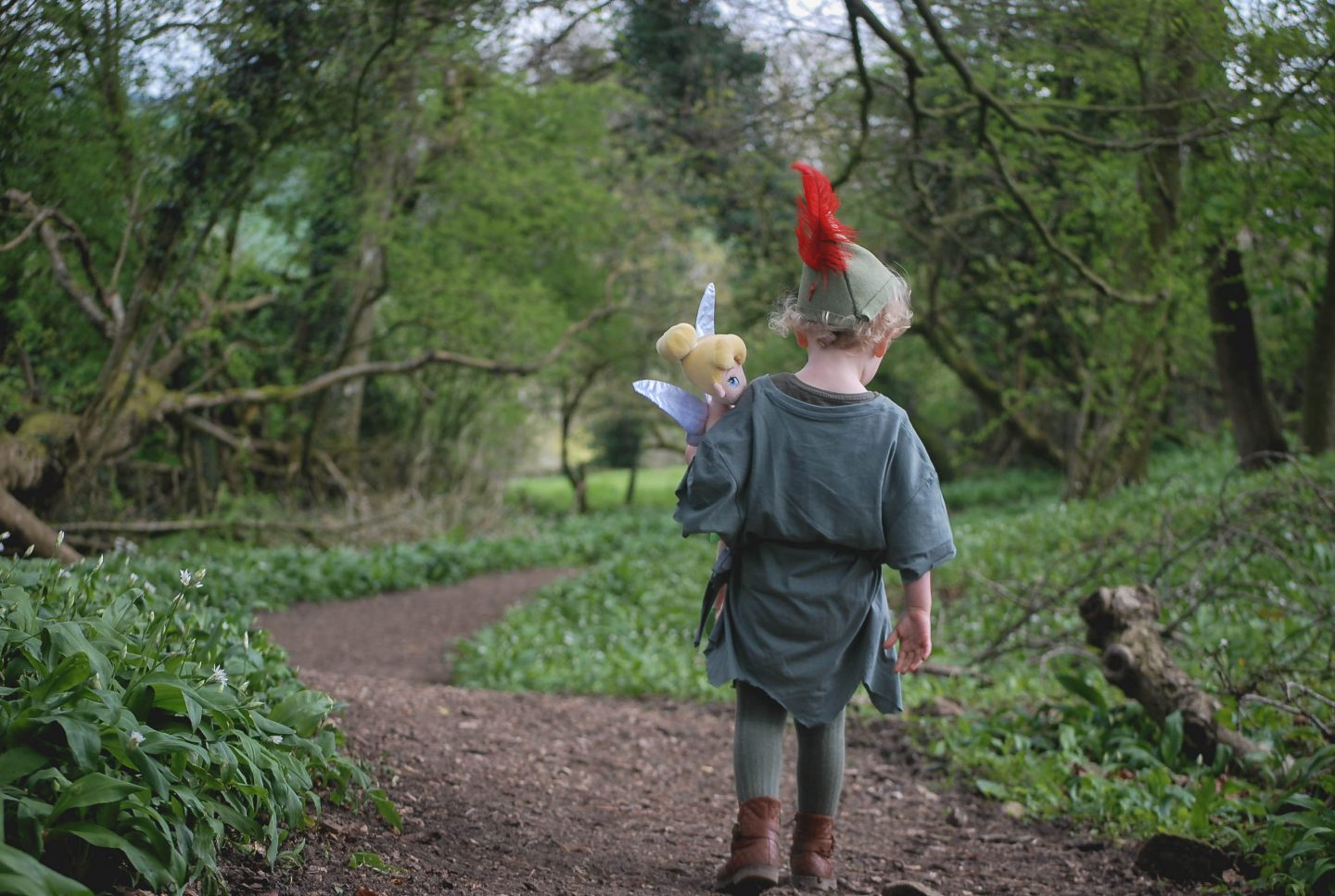 My daughter walking through the woods dressed as Disney's Peter Pan and carrying Tinkerbell